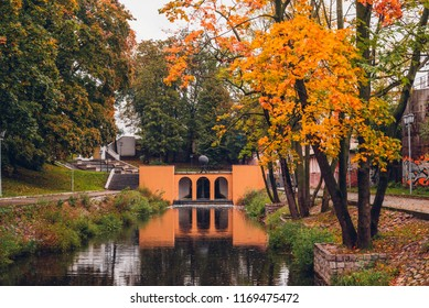 Beautiful lake in the picturesque park in rainy autumn day in Kaliningrad, Russia. Autumn foliage reflected in the water of the pond.