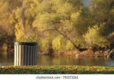 A beautiful lake scene in autumn with the leaves falling.  A clean modern trash can is in the focused foreground.