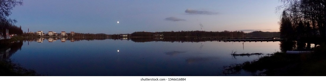 Beautiful lake scene panorama at night. Calm water and the moon on the clear sky.
