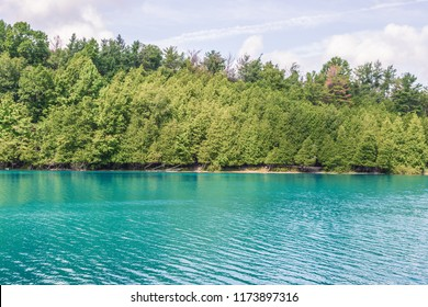 Beautiful lake scene, with a tree lined shore and turquoise water, taken in Syracuse NY, USA.