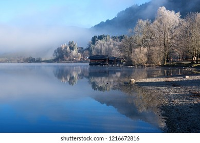 beautiful lake schliersee with boathouse and water reflection. early wintertime with hoarfrost.