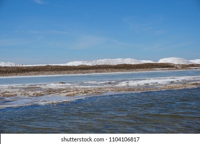 Beautiful lake shore on spring day with ice and snow in water, blue sky in the background