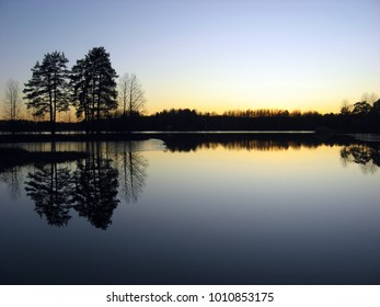 Beautiful lake shore reflecting in water after sunset