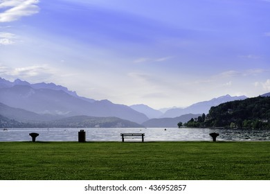 Beautiful lake surrounded by Alps mountains and bench on the grass