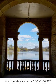 A beautiful lake is viewed through the window of a temple or summerhouse, its pillars in silhouette against the calm blue water and sky