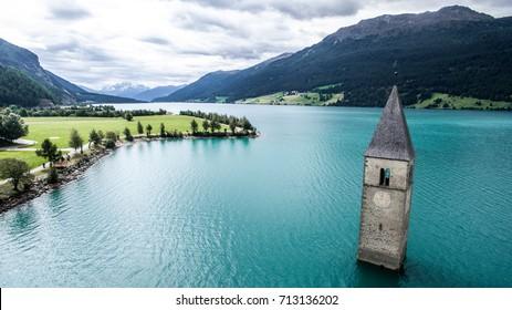 Schöne Landschaft mit dem Uhrturm in Reschensee. Lage Reschenpass an der Grenze zwischen Südtirol, Italien und Österreich.