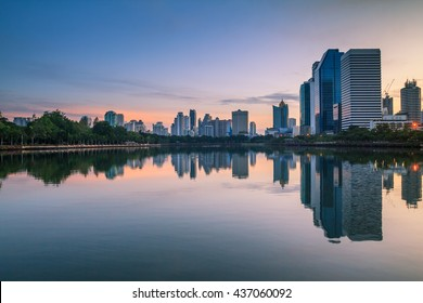 Beautiful landscape abstract city blur background and The light of sun reflection building on water.Panoramic and perspective wide angle  skyscraper commercial modern city of future. pastel concept.