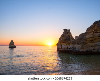 Beautiful landscape with amazing sunrise on the rocky atlantic ocean coast within the Lagos, Portugal. Popular summer travel destination and famous beach with coastal cliffs - Ponta da Piedade