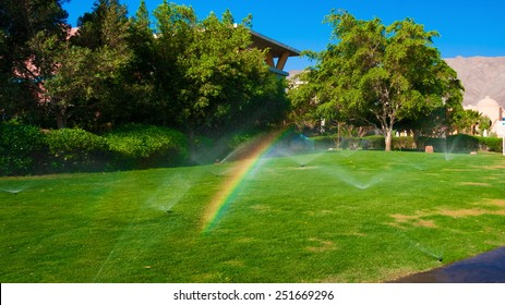 beautiful landscape with automatic  sprinkler spraying  watering the lawn in the home garden with a rainbow in water drops