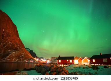 Beautiful landscape background of green arctic aurora borealis, northern light with magnetic polar dark night sky, stars, snow mountain and red houses in Hamnoy, Lofoten Norway