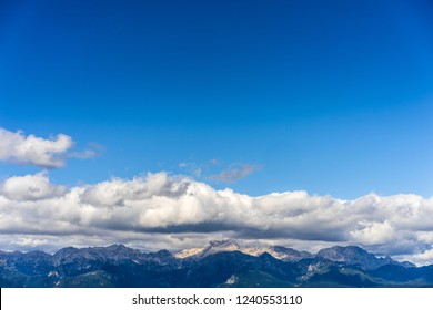 Beautiful landscape and background photo of alpine mountain landscape of Kamnik Savinja alps, Slovenia. Blue sky, white clouds and high alpine peaks and summit of Skuta, Grintovec and others.