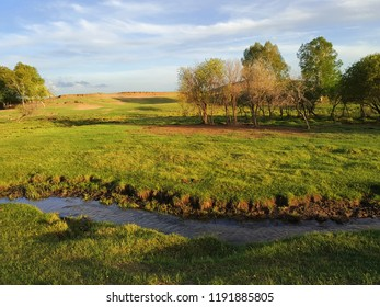 Beautiful landscape of a blue river, green grass lands and forest