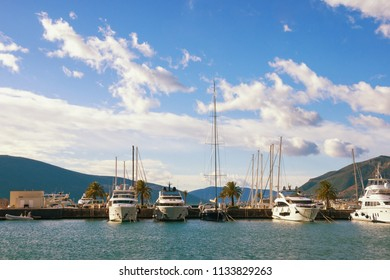 Beautiful landscape with blue sky, white clouds and line of yachts. Montenegro, Tivat, view of yacht marina of Porto Montenegro