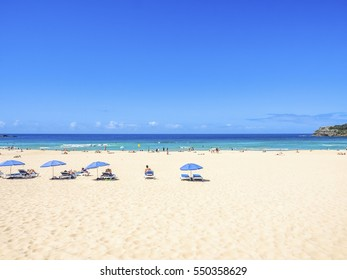 Beautiful Landscape in Bondi Beach, Australia. Blue Sky, White Sand, and Sunbathers.