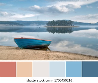Beautiful landscape, bright blue fisherman boat on orange beige sand, grey clouds in light blue sky over lake. Color palette swatches, pastel fashion trends in color combination inspired by nature.