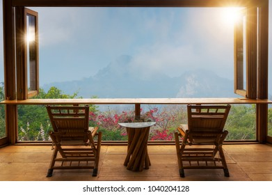 Beautiful landscape at cafe style minimal with wood tables and chairs terrace against the outdoor Mountain view in cafe at sunrise.