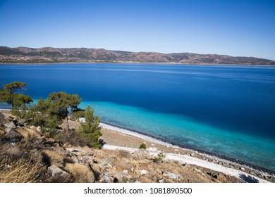 beautiful landscape with calm blue water and rocky coast, salda golu, turkey