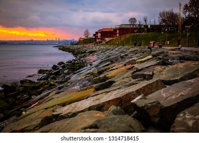 A beautiful landscape contains a rocks on the shore of the sea with a colorful catchy sky