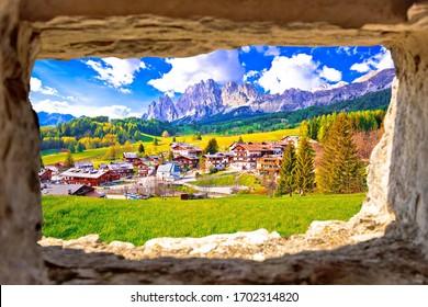 Beautiful landscape of Cortina d' Ampezzo in Dolomites Alps view through stone window, Veneto region of Italy