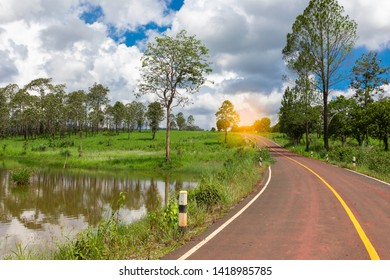Beautiful landscape of country road, there are water and mountains around and forest with cloudy blue sky background in Thung Salaeng Luang National Park Phetchabun, Thailand.