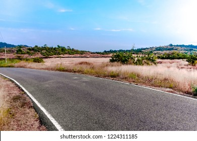 Beautiful landscape of countryside during long drive comprising barren lands, single landed asphalt road, dry grass, distant mountains, clear blue sky; on hot and bright sunny day.