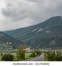Beautiful landscape, countryside scenery of a rural sight, hills in dramatic clouds on background. Road towards Shipka town, Balkan Mountains, Bulgaria. Travel and nature concept.