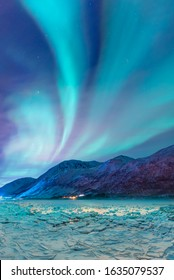 Beautiful landscape cracking ice, frozen norwegian sea coast - Northern lights (Aurora borealis) in the sky over Tromso, Norway