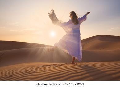Beautiful landscape in desert. Amazing dune Moreeb in United Arab Emirates. Golden waves of sand. Nature safari panorama. Woman enjoys view Liwa. Unique travel.