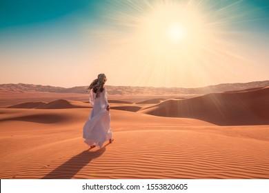 Beautiful landscape in desert. Amazing dune Moreeb in United Arab Emirates. Golden waves of sand. Nature safari panorama. Sexy woman enjoys view Liwa oasis. Unique travel.