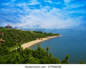 Beautiful landscape of distant town in China. There are seaside and beautiful sky. In spite of remoteness lots of windmills is important part of the townâ??s life.