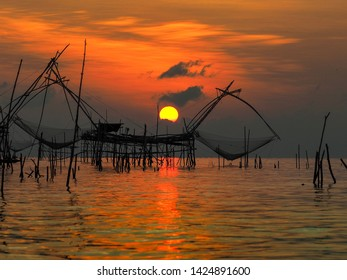 "Beautiful landscape during golden hour of sunrise in the morning at Ban Pak Pra, fisherman village, Phatthalung. A run rising in the middle of big fishing tool called ""Yor"", give a beautiful image."