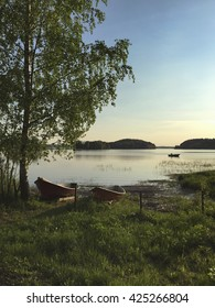 Beautiful landscape in Finland during early summer evening. A local fisherman is in the background fishing in a boat.