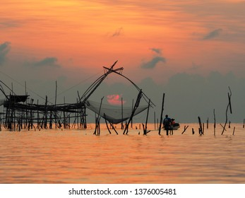 "Beautiful landscape with fishing tool called ""Yor"" and boat of tourists in the sea during sunrise at fisherman village, Ban Pakpra, Phatthalung, south of Thailand."