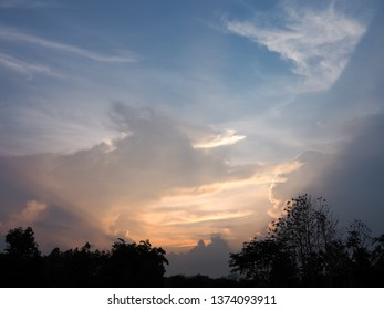 beautiful landscape of golden and blue clouds on sky and tree silhouetted after sunset for wallpaper or background