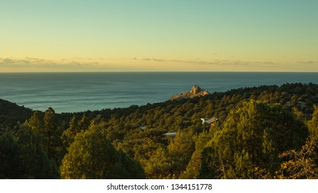 beautiful landscape of gorgeous nature, horizon between sea and blue sky during sunset, green trees, hills
