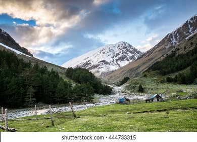 Beautiful landscape of green valley in the Caucasus mountains. In the foreground a small triangular wooden shelter and benches, then fence and house. Russia