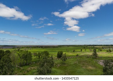 Beautiful landscape of green walley with some trees, deep blue sky and white clouds