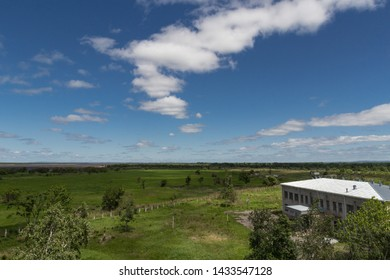 Beautiful landscape of green walley with some trees, deep blue sky with white clouds and small brick house from side