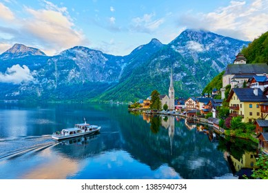 Beautiful landscape of Hallstatt mountain village with Hallstatter lake and boat in Austrian Alps. Austria, Salzkammergut region.