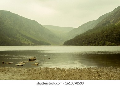 Beautiful landscape from the heart of Glendalough valley in a foggy day, with mountains reflecting in the water of the Lower lake. Irish Scenery. Grey sky. Wicklow National Park, Ireland