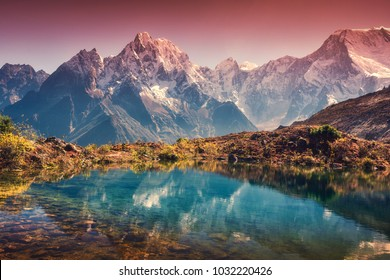 Beautiful landscape with high mountains with snow covered peaks, red sky reflected in lake. Mountain valley with reflection in water in sunset. Nepal. Amazing scene with Himalayan mountains. Nature
