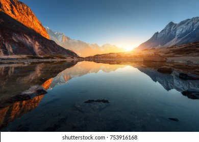 Beautiful landscape with high rocks with illuminated peaks, stones in mountain lake, reflection, blue sky and yellow sunlight in sunrise. Nepal. Amazing scene with Himalayan mountains. Himalayas