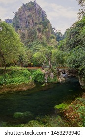 Beautiful landscape of a hill, small river and lush vegetation next to the Tham Chang (or Jang or Jung) Cave in Vang Vieng, Laos.
