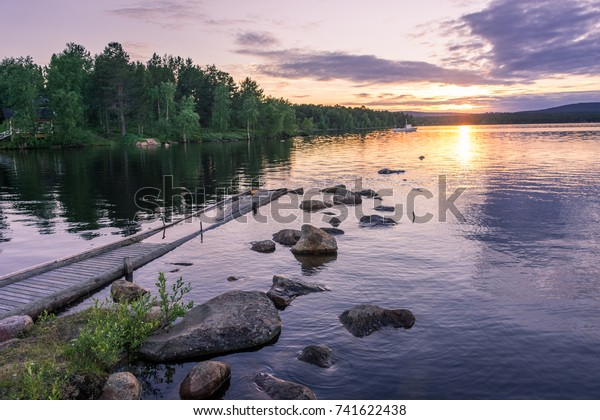 Beautiful landscape of the Inari Lake during the midnight sun, with wooden pier, finland, lapland