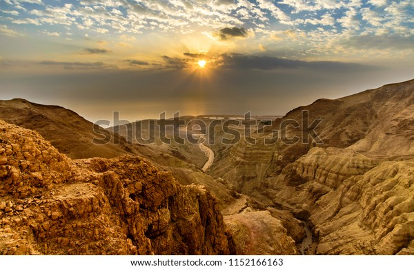 Beautiful landscape of Israeli Judean Desert mountains, with sunrise over the dry riverbed of Nahal Dragot Wadi, popular hiking trail winding between rugged rocky cliffs towards the Dead Sea
