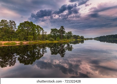 Beautiful landscape of the lake at colorful sunset. Dramatic sky in orange and purple colors. Panoramic view of the backwater and green coast with trees reflecting in the water.