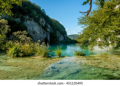 Beautiful landscape with lake. In the foreground a pond with clean, clear and emerald water where you can see the bottom of the lake. In the background the white cliffs.   Croatia - Plitvice lakes
