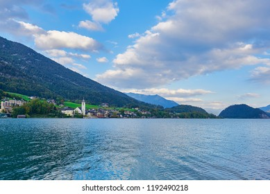 Beautiful landscape with lake, mountains, forest, clouds, house and reflection in water. Austria, Salzkammergut, Wolfgangsee.