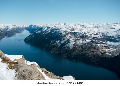 Beautiful landscape of lake, river, sea with the rocky shore with mountains with snowy peaks. Top view of the Pulpit Rock, Preikestolen. Lysefjord, Norway