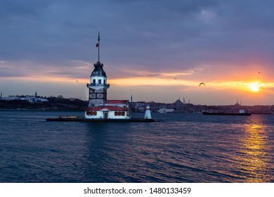Beautiful landscape of Maiden's tower (Tower of Leandros) at sunset. View of Dramatic cloudy sky. In the distance are such landmarks as Hagia Sophia, Blue Mosque and Topkapi Palace. Istanbul. Turkey.